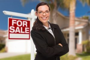 kozzi-13651222-young_woman_in_front_of_house_and_sale_sign-2395x1586
