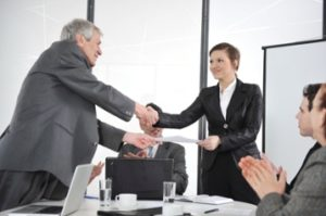 kozzi-2103878-happy_business_leaders_handshaking_at_meeting-884x588